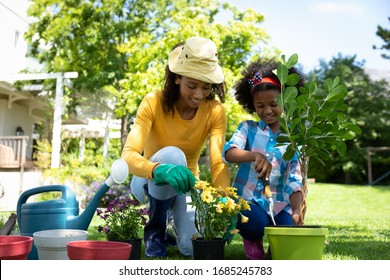 Front view of an African American woman and her daugther in the garden, kneeling and potting plants. Social distancing and self isolation in quarantine lockdown for Coronavirus Covid19