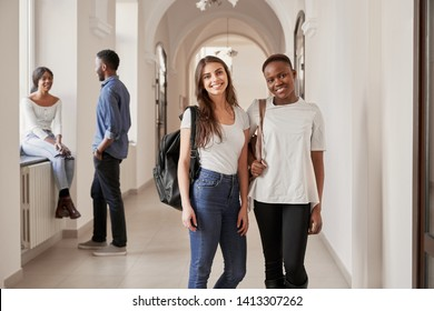 Front view of African and Caucasian female students resting on corridor and smiling at camera. Pretty women keeping friends, studying in international university. Concept of international friendship.