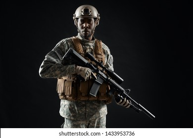 Front view of African male soldier wearing army uniform holding weapon in hands and confident looking at camera. Carriages man preparing for war. Concept of army. Black background.