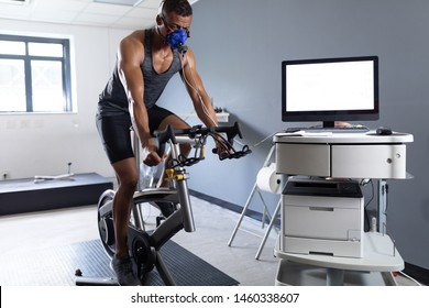 Front view of an African-American athletic man doing a fitness test using a mask connected to a monitor while riding an exercise bike inside a room at a sports center. Athlete testing themselves with
