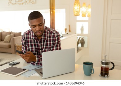 Front view of African-american man using mobile phone and laptop at table in a comfortable home. Working from home in quarantine lockdown. Social distancing Self Isolation
