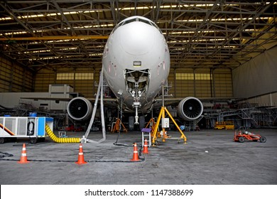 Front view of aircraft (airplane) lift up from the floor by aircraft jack for maintenance at aircraft hangar.Aircraft on jack in hangar for maintenance service check by mechanic.