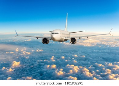 Front view of aircraft in flight. The passenger plane flies high above the clouds and blue sky. Business travel and summer trip concept