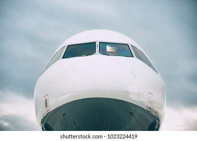 Front view of the airplane nose against cloud sky.