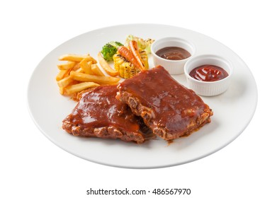 Front view of American style barbecue ribs steak with french fries, grilled vegetables, pepper sauce, and ketchup in ceramic dish isolated on white background