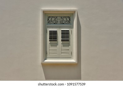 Front view view of antique window with wooden shutters and ornate carvings on the white wall of a house in Singapore as vintage background with space for copy.