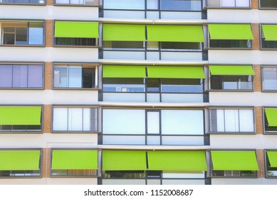 Front view of apartment house with lime green awnings, Netherlands.  Protection against sunlight, rising temperatures and heat waves in summer season