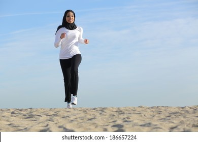 Front view of an arab saudi emirates woman running on the beach with the horizon in the background