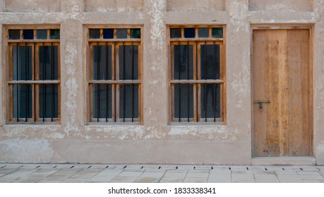 Front view of an Arabic old wall with traditional wooden windows and door. Arabic Style
