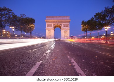 Front view of Arc de Triomphe (Arch of Triumph) in Paris at dusk with traffic light trail