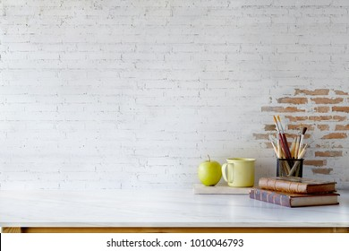 Front view of Artist or Designer desk with creative tools, vintage books and coffee mug over white brick wall. copy space for product display montage.