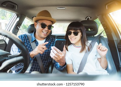 Front view asian couple happiness sitting in car and looking at smartphone. Travel concept, Safety first insurance concept