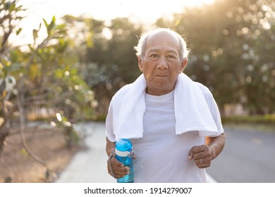Front view Asian elderly exercise. Close up Senior man holding water bottle running on road in public park that has sunshine in the evening. health lifestyle and exercise Concept.