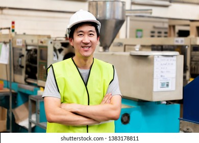 Front view of Asian factory worker with safety hard hat posed looking at camera with happy smile in industrial facilities at heavy industry factory