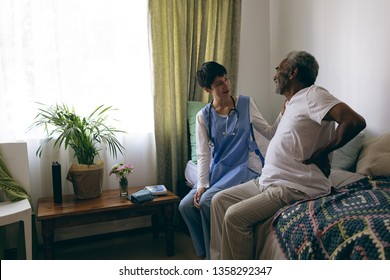 Front view of Asian female doctor and African-american senior male patient interacting with each other at retirement home. Senior male touches his back to show that it hurts.