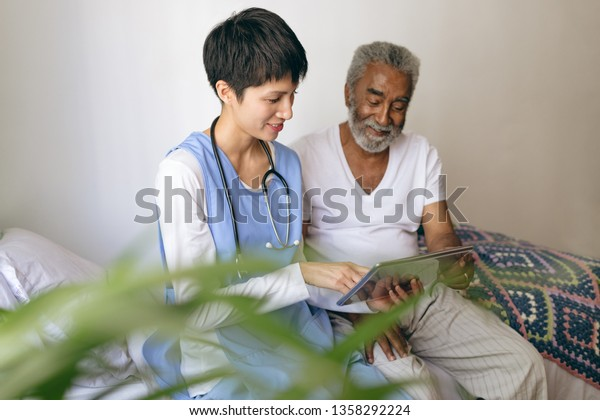 Front view of Asian female doctor and senior African-american male patient using digital tablet at retirement home