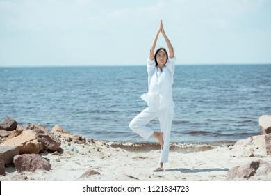 front view of asian woman standing in asana vrikshasana (tree pose) on beach by sea