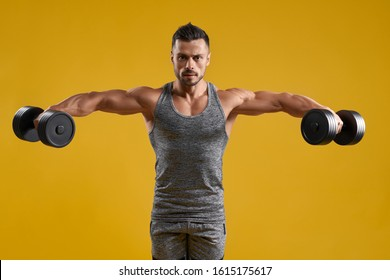 Front view of athletic gentleman in sport tank top lifting heavy weights. Handsome bodybuilder holding dumbbells and looking at camera with serious expression. Isolated on yellow studio background.