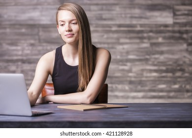 Front view of attractive girl in black tank top using laptop on wooden desktop with notepad