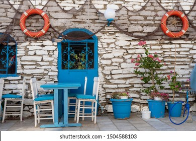 Front view of beach cafe exterior. Table and empty chairs outdoor near the stone wall. Tourist places. Typical Mediterranean restaurant, a place holidays in the summer. Bodrum, Turkey. Close up