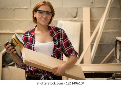 Front view of beautiful and attractive woman wearing safety glasses, standing and smiling. Talented craftswoman looking at camera and posing with electric sander and lumber.