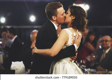 Front view of beautiful caucasian bride and groom passionately kissing with closed eyes at illuminated patio in front of guests, friends and relatives. Concept of marriage, love and desire.