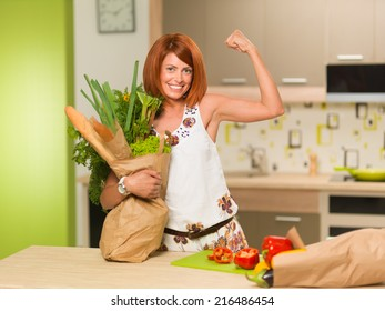 front view of beautiful caucasian woman standing in kitchen, smiling, holding bag with groceries, showing her arm muscles