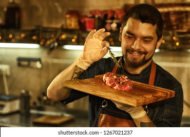 Front view of beautiful chef holding wooden cutting board with meat. Man in apron and white gloves smiling and looking at meat. Background of professional restaurant kitchen.