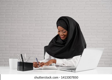 Front view of beautiful female wearing black hijab smiling and writing while sitting at table at office. Young african woman smiling and enjoying working process in company. Concept of business.