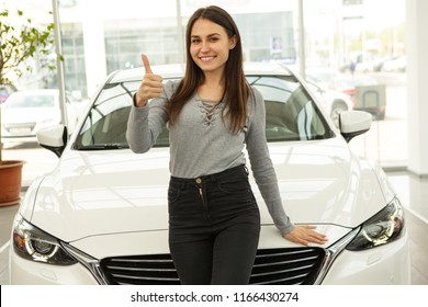 Front view of beautiful and gorgeous girl standing before her new white car. Happy owner of new automobile she buying in modern car dealership. Young woman smiling and showing thumb up/