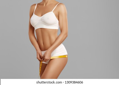 Front view of beautiful slender model holding measure tape in hands and taking measurements of her body. Gorgeous and sexy woman posing and standing, wearing white underwear.