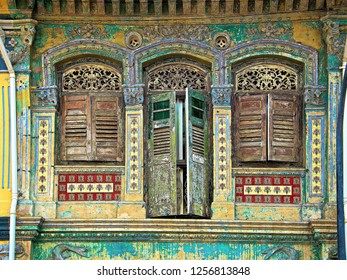 Front view of beautiful traditional Singapore shophouse with distressed exterior, antique wooden shutters and strong tones and textures in historic Geylang