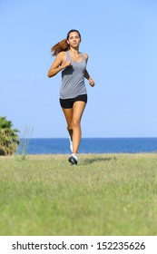 Front view of a beautiful woman running on the grass with the sky and the sea in the background