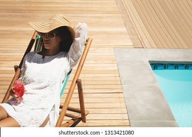 Front view of beautiful young African American woman with cocktail glass relaxing on sun lounger in backyard on a sunny day. She seems to be on vacation