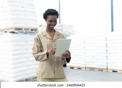 Front view of beautiful young African-american female worker working on digital tablet in warehouse. This is a freight transportation and distribution warehouse. Industrial and industrial workers