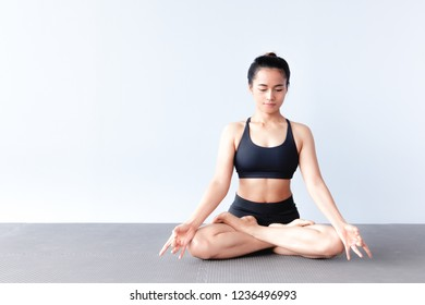 Front view of beautiful young asian woman wearing sportswear practicing yoga in studio,natural light.Concept : Variation yoga poses.Lotus pose ( Padmasana).Copy space for text.