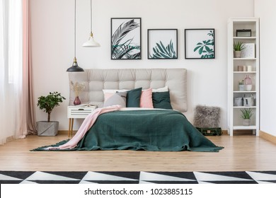 Front view of bedroom interior with double bed decorated with pillows, white shelf and botanical posters