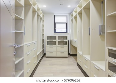 Front view of big dressing room with big wardrobe with many shelf and basket. Empty room with furniture for many clothing.
