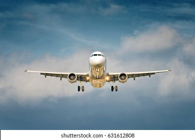 Front view of a big jet plane taking off on blue cloudy sky background