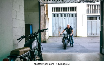 Front view of biker taking custom motorbike to the garage