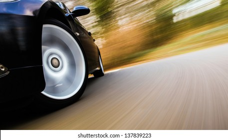 Front view of black car in turn  with heavy blurred motion.