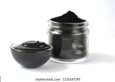 Front view of black cosmetic activated charcoal powder and beauty face mask  mixture on white. Oily skin, detox and acne treatment.