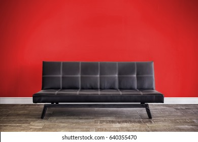 Front view of black leather sofa in interior.