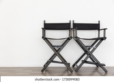 front view of black two director chair in film industry on wooden floor with white wall background