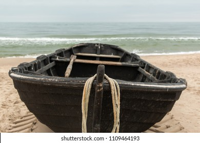 Front view of a black wooden fishing boat, sea in background and copyspace