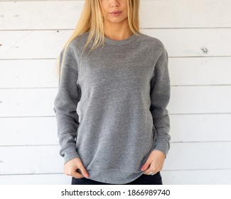 The front view of blond hair woman wearing a grey hoodie or blouse. She is standing on white board. Fashion outfit for mockup.  Sweatshirt template.