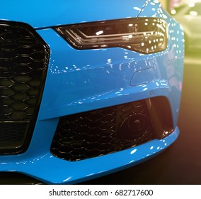 Front view of blue modern luxury sport with soft orange sun light. Car exterior details. Headlight of a modern sport car. The front lights of the car