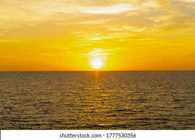 Front view in the blue ocean in the evening, the sun was setting, reflections fell on the smooth calm surface with golden warm light. The sky is clear and clean. Feeling refreshed and relaxed.
