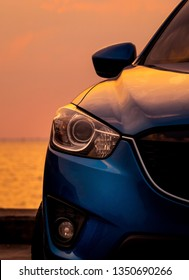 Front view of blue SUV car with sport and modern design parked on concrete road by the sea at sunset in the evening. Closeup headlamp light of blue car.  Hybrid and electric car technology concept.
