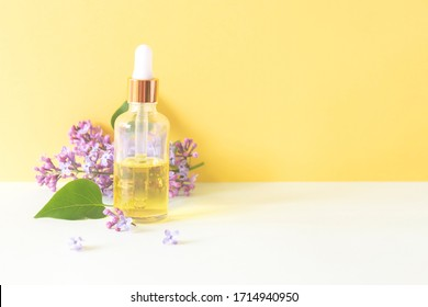 front view of bottle of beauty oil with lilac flowers on yellow background with copy space nature beauty remedy